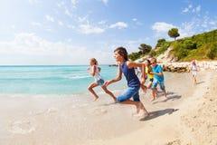 Happy kids run on the edge of sea Royalty Free Stock Image