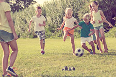 Group of active kids playing football together on green lawn in Royalty Free Stock Image