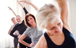 Group of senior people doing exercise in community center club. Group of active senior people doing exercise in community center club stock photo
