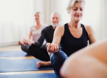 Group of senior people doing yoga exercise in community center club. royalty free stock photography