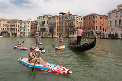 Group of active tourists stand up paddling on sup boards at Grand Canal, Venice, Italy. Royalty Free Stock Photos