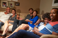 Group of adult friends watching television together royalty free stock image