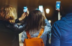 Group adult hipsters using in hands mobile phone closeup, online wi-fi internet concept in street, bloggers friends together point. Ing finger on screen royalty free stock photos