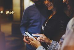 Group adult hipsters using in hands mobile phone closeup, street online wi-fi internet concept, bloggers friends together pointing. Finger on screen smartphone royalty free stock images