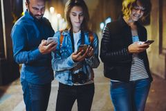 Group adult hipsters using in hands mobile phone closeup, street online wi-fi internet concept, bloggers friends together pointing. Finger on screen smartphone stock photo