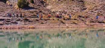 Group of adult people with colorful backpack trekking on a path of sand and stones walking next to a lake reflecting their images. Group of adult people with stock photos