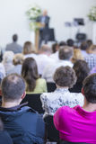 Group of Adult Professionals Listening to the Lecturer Speaking on Stage Stock Photo