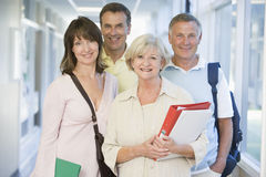 A group of adult students standing in a corridor Royalty Free Stock Images