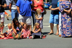 Group of adults and children waiting on sidewalks for the holiday parade, Saratoga Springs, New York, 2016 Royalty Free Stock Image