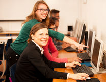 Group of adults learning computer skills. Intergenerational tran. Sfer of knowledge Stock Image