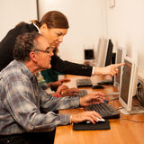 Group of adults learning computer skills. Intergenerational tran Stock Images