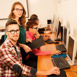 Group of adults learning computer skills. Intergenerational tran Stock Image