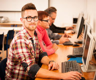 Group of adults learning computer skills. Intergenerational tran Royalty Free Stock Images