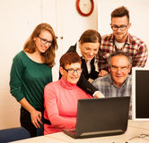 Group of adults learning computer skills. Intergenerational tran. Sfer of knowledge Royalty Free Stock Image