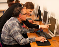 Group of adults learning computer skills. Intergenerational tran. Sfer of knowledge Stock Photo