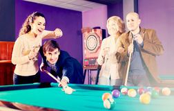 Group of adults playing pool. Smiling middle class adults having pool game in billiard club. Selective focus Stock Images