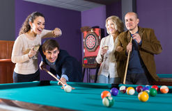 Group of adults playing pool. Smiling middle class adults having pool game in billiard club. Selective focus Stock Photo