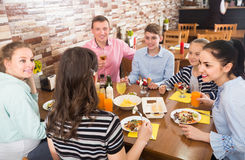 Group of adults and teenagers spending time in  cafe Stock Images