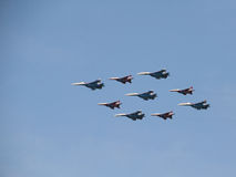 Group aerobatics of fighters SU on parade. Fighters group aerobatics demonstrates a mastery of military pilots. The planes fly at a distance of 5-7 meters from stock image