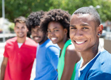 Group of african american and latin young adults in city. With buildings and green plants and trees in the background stock photography