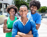 Group of african american young adults with crossed arms. In the city with buildings and green plants and trees in the background royalty free stock photography