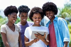 Group of african american young adults reading news with digital tablet. Outdoor in the summer royalty free stock images