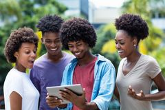 Group of african american young adults shopping online with digital tablet. Outdoor in the summer stock images