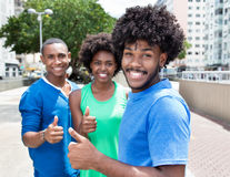 Group of african american young adults showing thumb. In the city with buildings and green plants and trees in the background stock photography