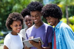 Group of african american young adults watching movie with digital tablet. Outdoor in the summer royalty free stock photo