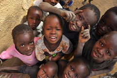 Group of african children smiling. Group of  black children making faces and looking curious in a village of Niger, West Africa Royalty Free Stock Image
