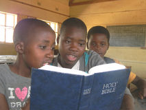 Group of African school kids  reading Bible. Stock Photo