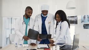 Group of professional doctors with x-ray of the patient discussing history of the disease at hospital. Hospital. Group of african young professional doctors with stock video