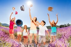 Happy kids tossing up hats over blue sky in summer Stock Photo