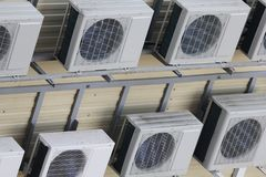 Group of air conditioners suspended on the wall stock photography