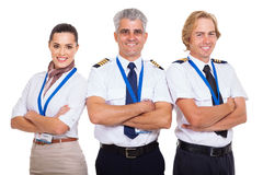 Group airline crew. Group of professional airline crew with arms folded on white background royalty free stock photography