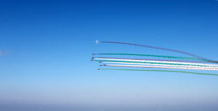 Group of airplanes with colored track red, white, green clouds on blue sky background, horizontal view. Colors of italian flag. stock photography