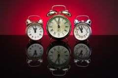 Group of alarm clocks, red background Royalty Free Stock Photography