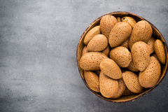 Group of almond nuts with leaves.Wooden background. Royalty Free Stock Photo