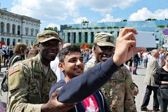 Group of american soldiers taking selfie with cywilians. Royalty Free Stock Photography