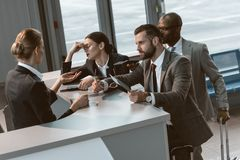 Group of angry businesspeople having argument. With airport receptionist royalty free stock photo
