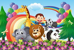 A group of animals at the hilltop with a rainbow and balloons Royalty Free Stock Photos