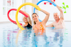 Group in aquarobic fitness swimming pool. Group  or young and senior people in aquarobic fitness swimming pool exercising with  pool noodle Stock Photography