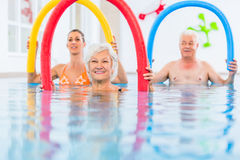Group in aquarobic fitness swimming pool. Group or young and senior people in aquarobic fitness swimming pool exercising with pool noodle stock image