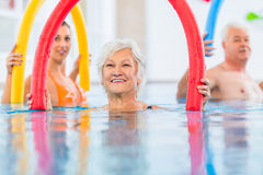 Group in aquarobic fitness swimming pool. Group or young and senior people in aquarobic fitness swimming pool exercising with pool noodle royalty free stock images