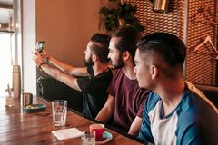 Group of arab friends taking selfie in lounge bar. Mixed race young men having fun. Best friends hangout together royalty free stock photo
