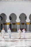 A group of arab men walking towards a mosque taken on April 01, 2013 in Abu Dhabi, United Arab Emirate Royalty Free Stock Image