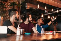 Group of arabian friends taking selfie in lounge bar. Mixed race young men having fun together. Group of arab friends taking selfie in lounge bar. Mixed race stock image