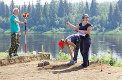 A group of archaeologists determines the coordinates of their findings using a total station. Editorial.Nyaksimvol village Beryozovsky district of the Khanty Royalty Free Stock Photos