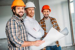 Group of architects with blueprint inside of constructing building looking. At camera royalty free stock images