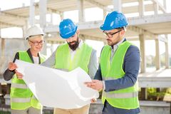 Group of architects or business partners discussing floor plans on a construction site. Mixed group of serious engineers or business partners at construction stock image